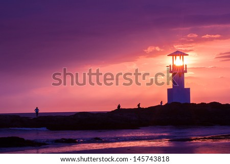 Lighthouse searchlight beam through marine at sunset. - stock photo