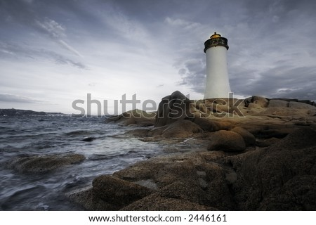 lighthouse seen from a tiny beach in Sardinia. - stock photo