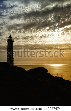 lighthouse silhouette with sunset - stock photo