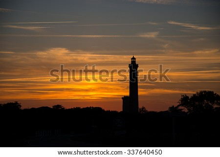 Lighthouse silhouette with sunset, France.