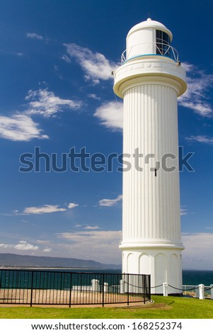 Lighthouse stands symbolically on green lawn under blue sky. Kiama, New South Wales, Australia. - stock photo