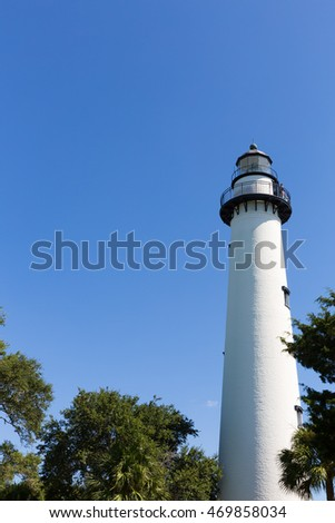 Lighthouse surrounded by trees against blue skies