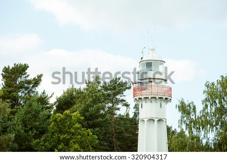 Lighthouse tower on the background of green trees