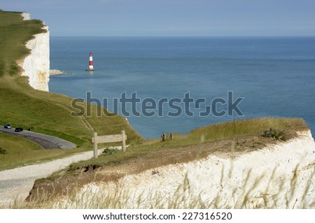 Lighthouse under the white chalk cliffs at Beachy Head near Eastbourne in East Sussex. England - stock photo