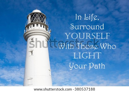 Lighthouse with a Inspirational motivational quote of In Life Surround Yourself With Those Who Light Your Path against a partly cloudy sky background - stock photo