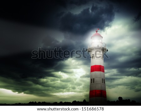Lighthouse with beam against dark stormy sky - stock photo