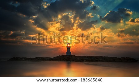 Lighthouse with light beam at sunset at Khao Lak - stock photo