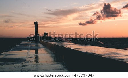 lighthouse with rusty metal rails near sea port  and silhouettes. - vintage film effect