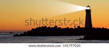 Lighthouse with searchlight beam at sunset - stock photo