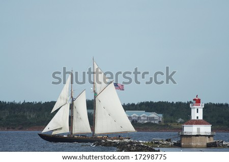 lighthouse with tall ship passing