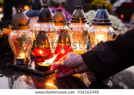 Lighting a candles at a cemetery during All Saints day. Shallow depth of field. - stock photo