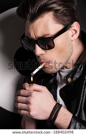 Lighting a cigarette. Handsome male model in leather jacket lighting a cigarette