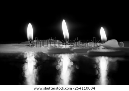 Lighting and reflection of candle, black and white - stock photo