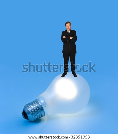Lighting lamp and man on blue background - stock photo