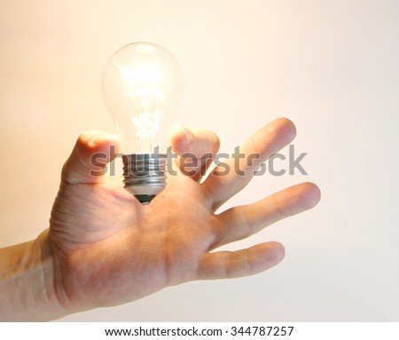 Lighting lamp flashing bulb in human hand on white background
