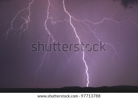 Lighting strikes through the night sky during a summer storm - stock photo