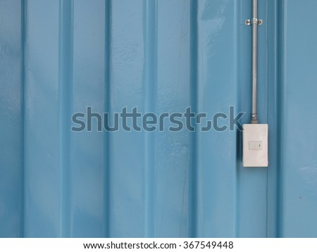 Lighting switch on the blue door, free text space for designer on the left. - stock photo