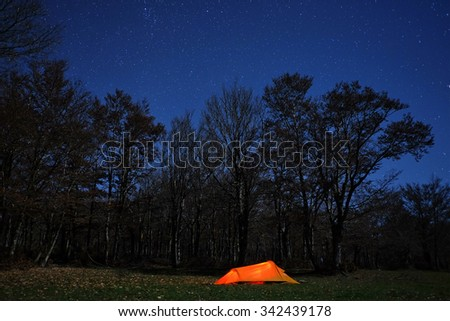 lighting tent, woods and blue starry night in Nebrodi Park, Sicily - stock photo
