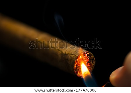 lighting up a cigar, black background - stock photo