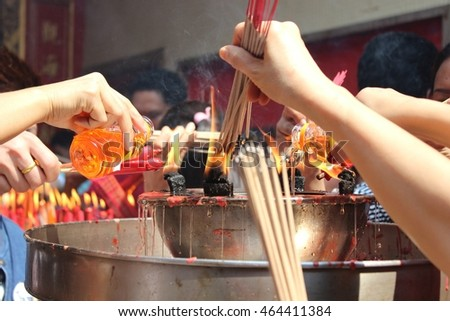 Lighting up the joss stick with fire flames and filling oil lamp merit