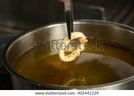 Lightly fried Calamari ring being taken out of a pan of hot oil. - stock photo