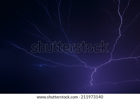 Lightning arcs in the night sky in dramatic fashion. - stock photo