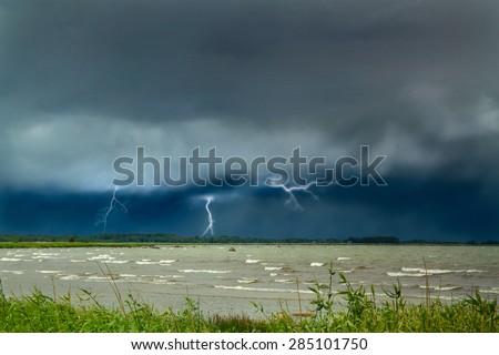 Lightning at sea. curtains on the coast. rainy weather - stock photo
