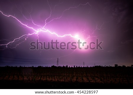 Lightning between clouds at night over electricity transmission power lines or cable (High voltage tower)