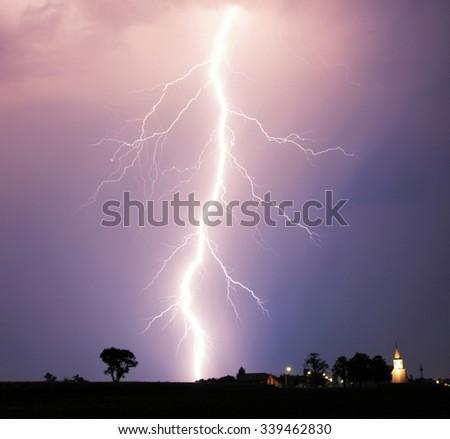 Lightning bolt at strom over village - stock photo