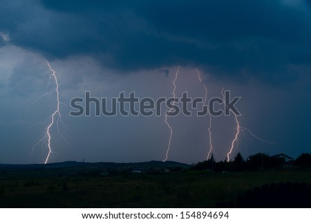 Lightning bolt striking in the sky from clouds - stock photo