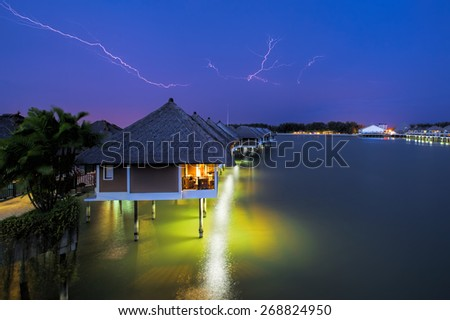 Lightning colouring the sky over waters villas at night - stock photo