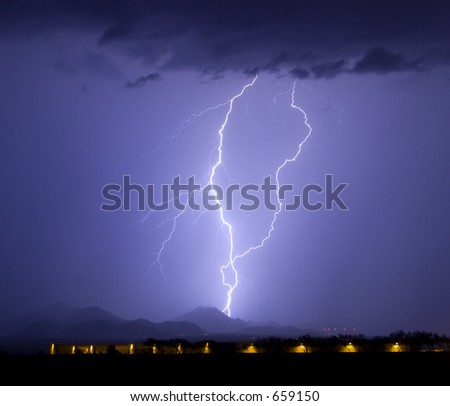 Lightning display in southwestern United States with airport hangers in the foreground - stock photo