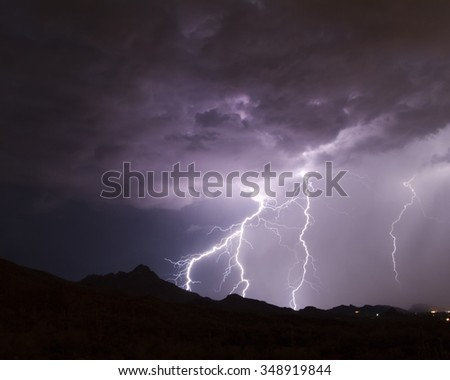 Lightning from a monsoon thunderstorm striking a mountainside in the Sonoran Desert outside of Tucson, Arizona.