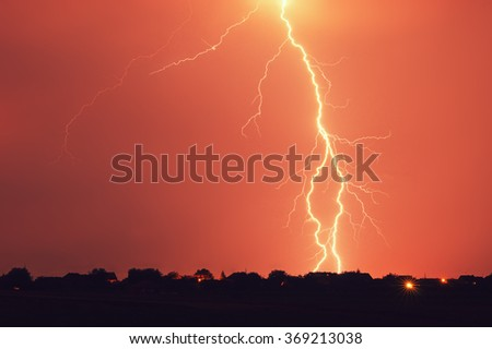 Lightning hits at stormy night - stock photo
