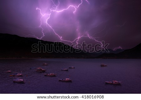 lightning in sea bay with boats - stock photo
