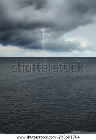 Lightning into the sea during a storm. dark clouds over water