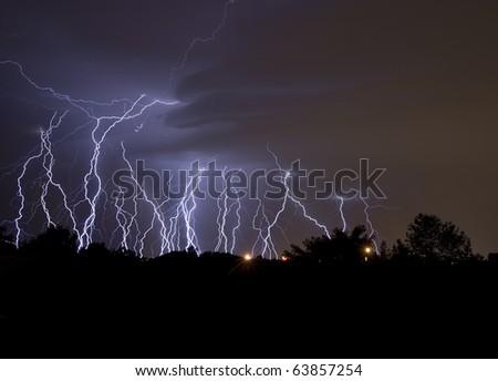 Lightning Multiple lightning strikes in a neighborhood at night. Horizontal. - stock photo