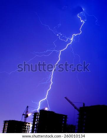 Lightning storm crane weather industrial city building construction night flash - stock photo