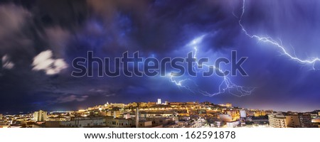 lightning storm in a city at night - stitched panorama - stock photo