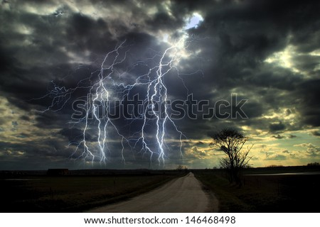 Lightning storm over asphalt road - stock photo