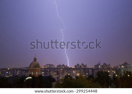 Lightning storm over city and church in purple light - stock photo