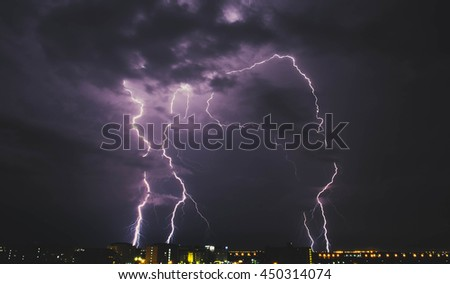 Lightning storm over countryside city at night in Thailand