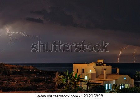 Lightning storm over sea and beach house - stock photo