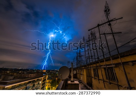 Lightning storm over the city. The lighting strikes on the horizon and breaks the clouds. The picture is taken from the top roof filled of aerials. - stock photo