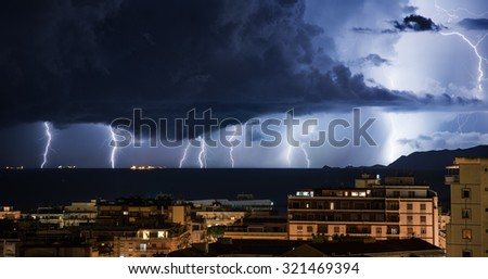 Lightning storm that hits the sea off the city - stock photo