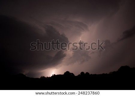 Lightning streaks across the night sky during a thunderstorm in the Midwest of the United States - stock photo