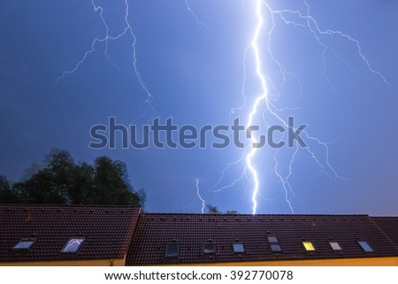 Lightning strike behind a house - stock photo
