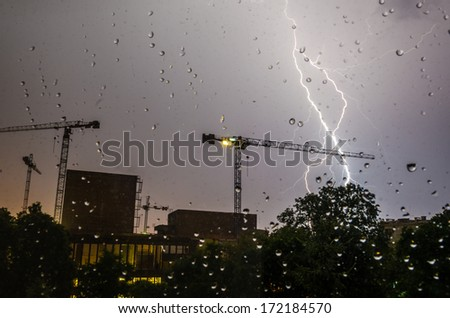 Lightning strike in a construction area viewed through glass with rain drops. - stock photo