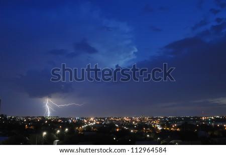 Lightning strike over night city - stock photo