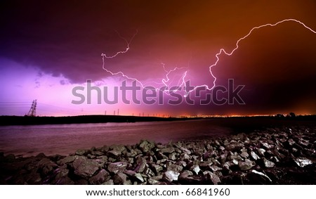 LIghtning Strikes over rocks and water - stock photo